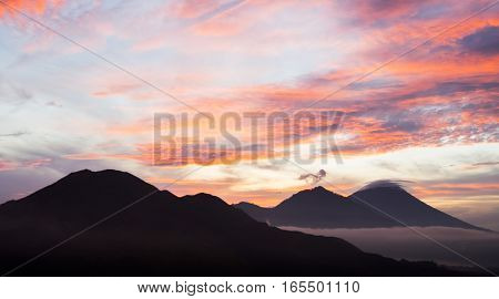 Sunrise in volcanic caldera of Batur Mountain with view to Batur, Agung and Abang volcanoes.