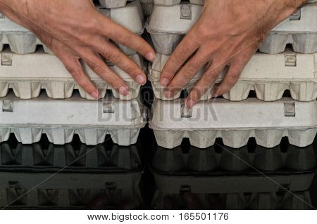 Man hands holding arranged egg boxes on a table