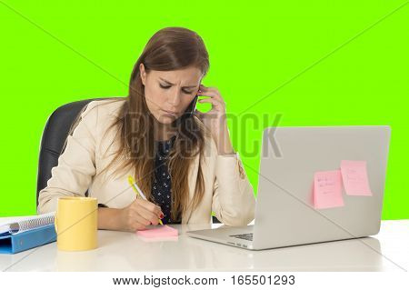 young attractive businesswoman in at office computer desk talking on mobile phone taking notes on pad in overworked secretary concept isolated green chroma key screen background