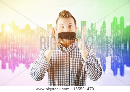 Young man in abstract rainbow city with no freedom of speech