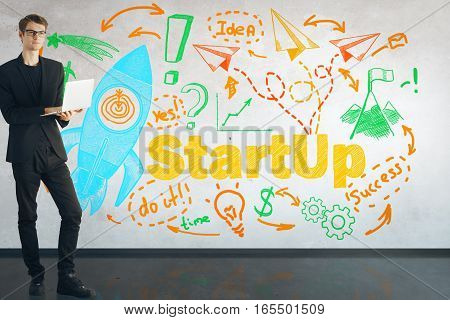 Young man using laptop in concrete room with startup sketch. Start up concept