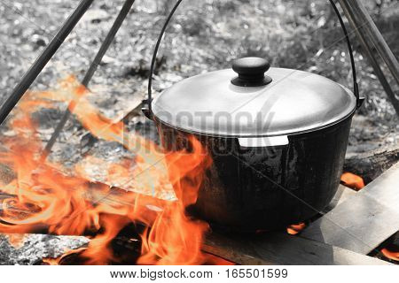 Pot for cooking on a fire / Black and white photo in retro style