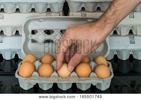 Man hand picking up an egg from egg box