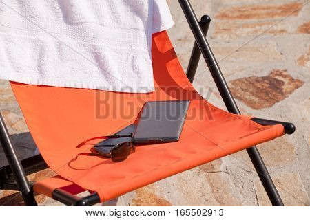 e-reader smart phone and sunglasses on beach chair (on vacation)