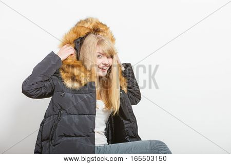 Beautiful smiling young fashionable girl wearing jacket with hood. Preparing herself clothes. Fashion in winter time.