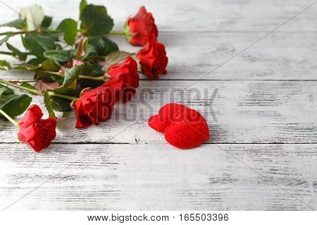 Bunch of red roses on white wooden table