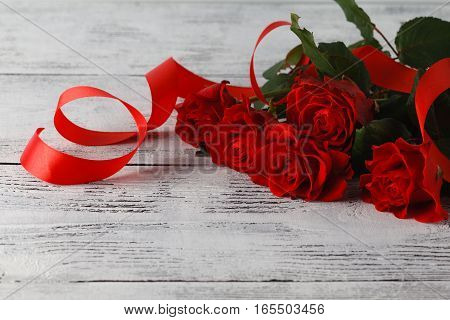 Bunch of red roses on table with red ribbon