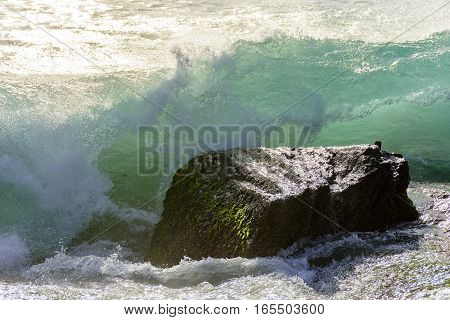 Waves breaking on the stone during sunset