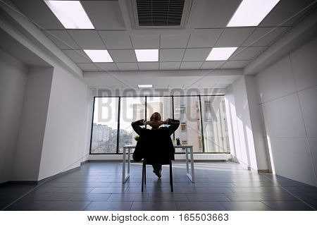 Businessman dreaming about the future. Man in business suit modern office raised his hands behind his head, staring out window with a view of city.
