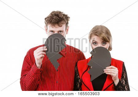 Love shame romance heartbreak depressing sadness relationship concept. Couple hiding their faces. Young man with woman holding broken heart parts in front of heads.