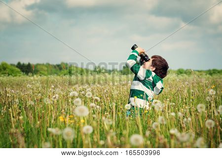 Child wathing in benoculars on the field with dandelions. Boy playing on the meadow in summer