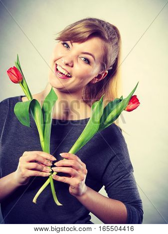 Happiness and satisfaction with life. Blonde woman wearing eyewear with single red green tulip. Happy joy girl feeling spring time holding beautiful flower.