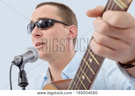 a young handsome man singing with sun glasses