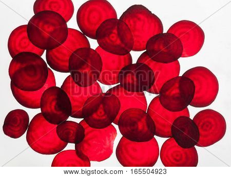 Backlit of red beetroot round slices on white, pattern for textured background. Abstract art composition of fresh organic vegetables