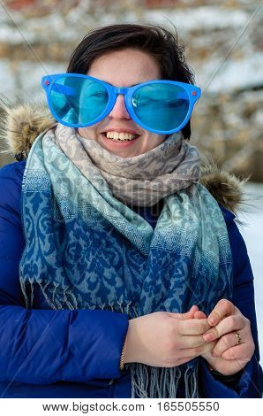 Brunette adult girl in big clown glasses and blue jacket with scarf, smiling, standing alone outdoor in the cold winter