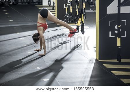 Amazing girl stands on the hands upside down on the floor in the gym. Her feet are on the TRX straps. She wears red top and sneakers, black shorts. Horizontal.