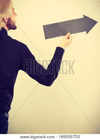 Planning directions choices concept. Man holding black arrow pointing right. Indoor shot on light background