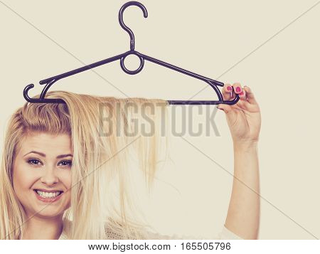 Hairstyle and haircare concept. Blonde woman with hair in clothes hanger.