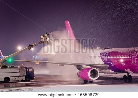 Deicing Passenger Airplane During Heavy Snow