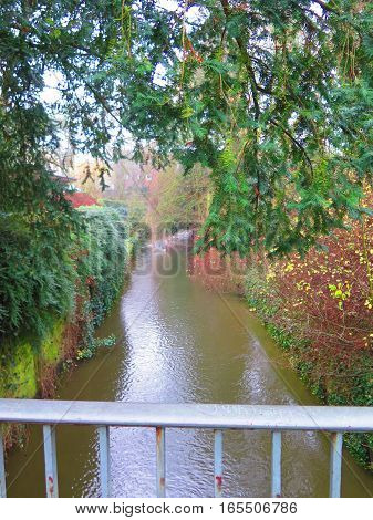 Urban scene with small stream flowing through German town of Munster