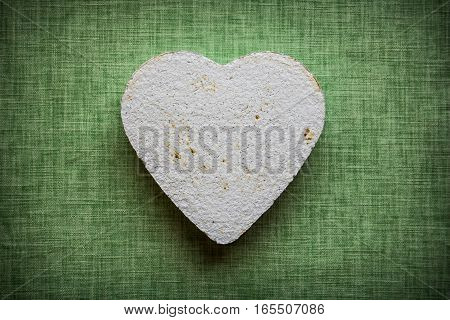 Heart made of paper mache on a fabric background to be used for crafts
