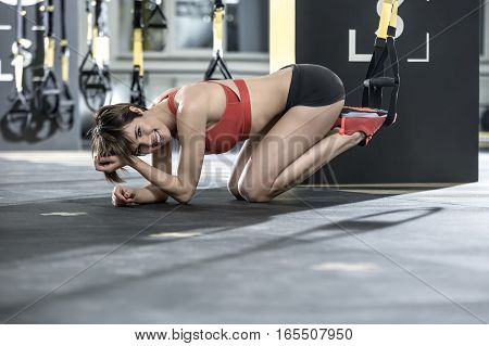 Joyful girl stands on the knees and elbows on the floor in the gym. Her feet are on the TRX straps. She wears red top and sneakers, black shorts. Woman looks into the camera with a smile. Horizontal.