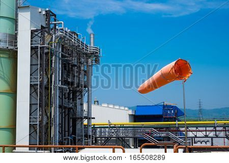 a windsock inflated by the wind on the sky against power plant background