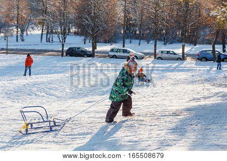 Families Enjoy Sledding On A Snowy Hill