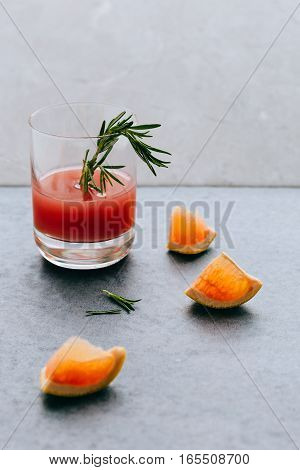 Freshly Squeezed Tropical Juice in Glass with Rosemary on Table