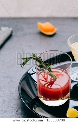 Vertical View of Red Drink in Glass garnished with Fresh Rosemary