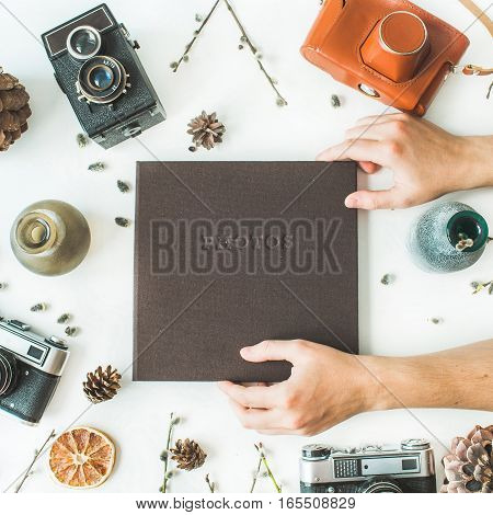 Brown wedding or family photo album hands cones vintage retro camera branches of willow leaves and dry oranges on white background. Flat lay top view