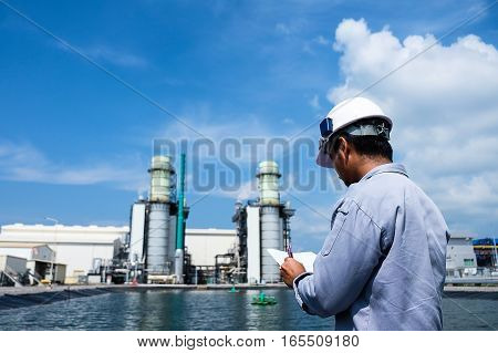 Engineer is recording data against combine cycle power plant background