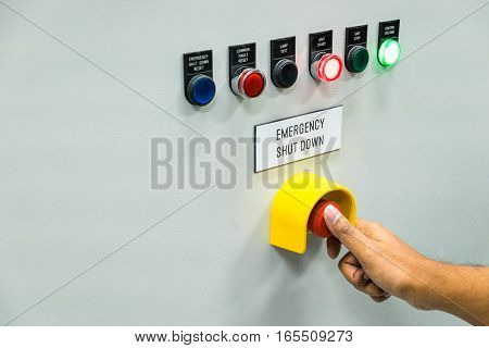 Technician is turning off emergency shutdown button on control panel in power plant