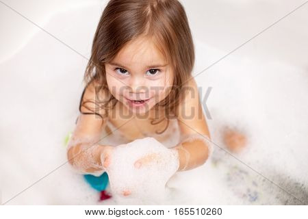 Funny baby girl playing with water, toys and foam