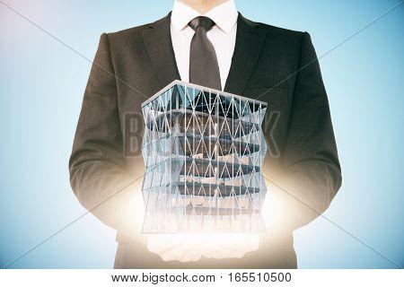 businessman holding modern skyscraper 3D Rendering. Close up.