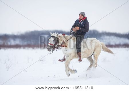 Pietrosani Romania - January 6 2017: People race their horses on a snowy field during a traditional Epiphany horse race in Pietrosani Romania.