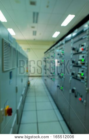 Blur photo of lit lights and control dials on manufacturing machinery in power plant or refinery plant