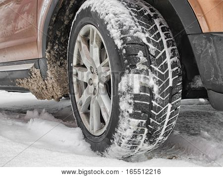Detail of car. Winter tire standing on road with snow