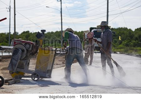 A worker cutting concrete road with diamond saw blade machine and cleaning