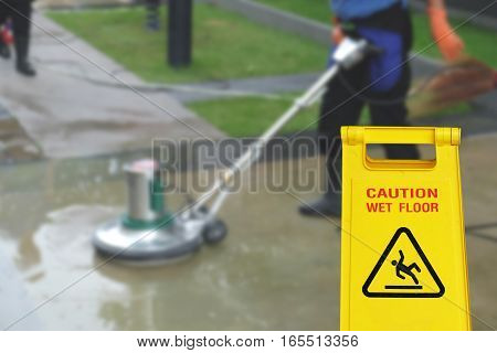 Cleaning in process and caution wet floor symbol against cleaning blur background