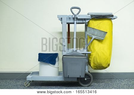 Yellow mop bucket and set of cleaning equipment in the airport