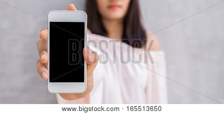 Smiling woman showing a blank smartphone screen standing on concrete wall. Natural style. Wearing white dress. Grey wall background.
