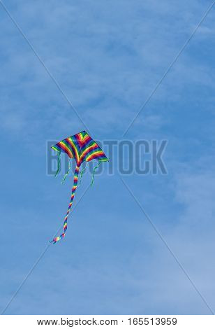 Lonely rainbow kite in blue sky .