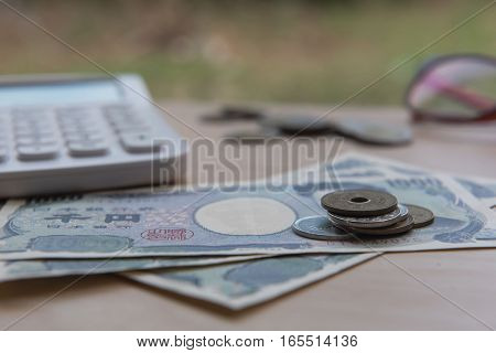 Closeup coin yen and banknotes Japanese and Calculator on wooden background. Currency of Japan.