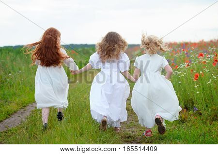 three young girls running together joined hands