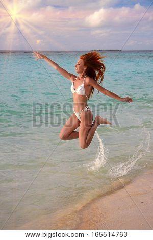 The woman jumps on an sea coast Maldives