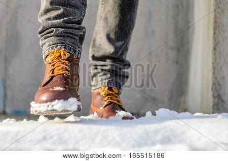 Man walks in the snow street. Feet shod in brown winter boots. Winter walks concept