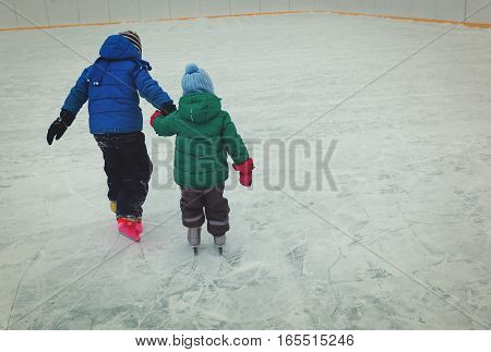 little boy and girl skating together in winter nature