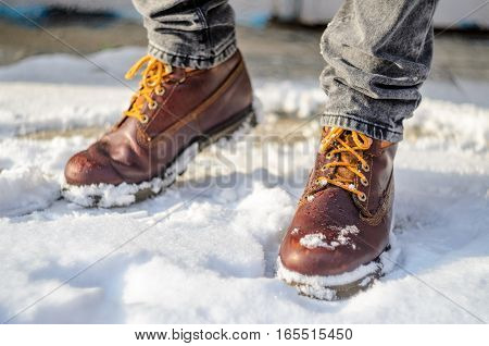 Man walks in the snow. Feet shod in brown winter boots. Winter walks concept