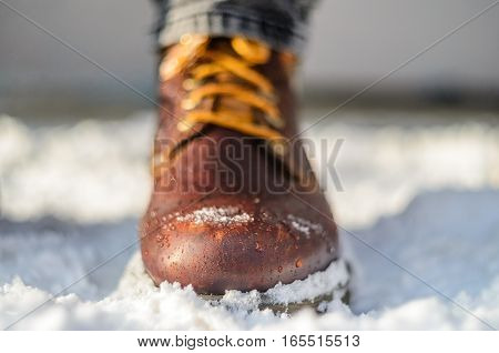 Snow melts on brown winter boots. Brown leather shoes in the snow. Shallow depth of field. Legs in the warmth concept.